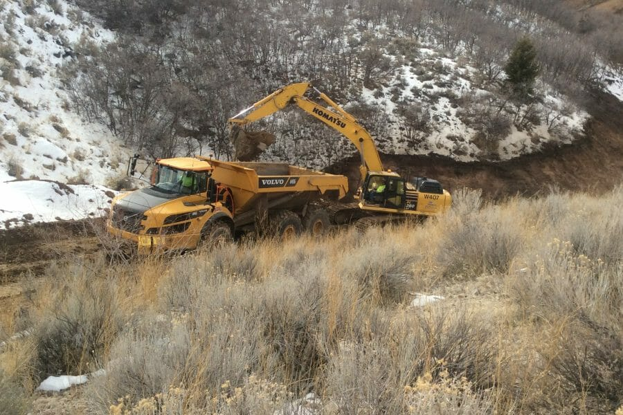 Excavator Digging on Snowy Hillside